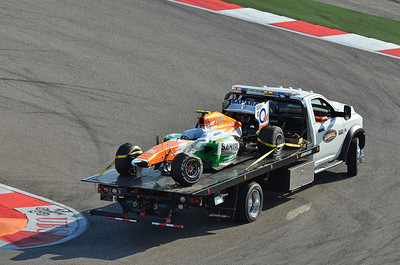 Adrian Sutil's damaged Force India car transported back to the pits after the race.